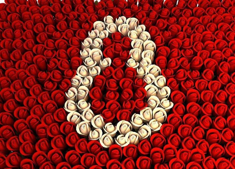 Цифра восемь сделанная из белых роз на фоне красных