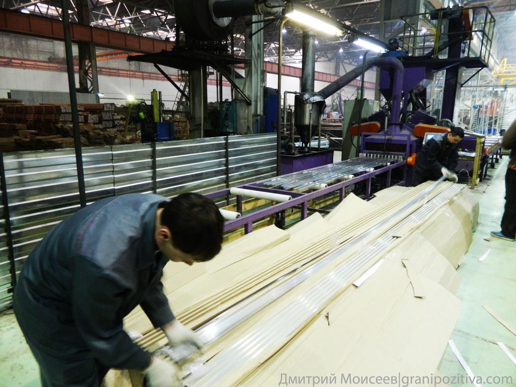 Рабочие укладывают профиль на специальные ролики на заводе Найди в Ижевске