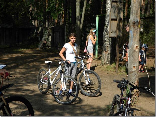 девушка держит велосипеды участников на соревнованиях по велокроссу Cross  Forest в городе Воткинск