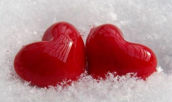 Два красных сердца на мягком снегу