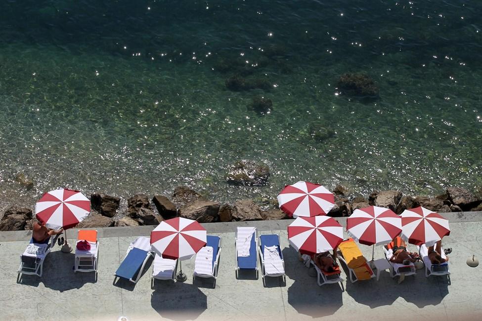 Шезлонги с зонтиками на каменистом пляже