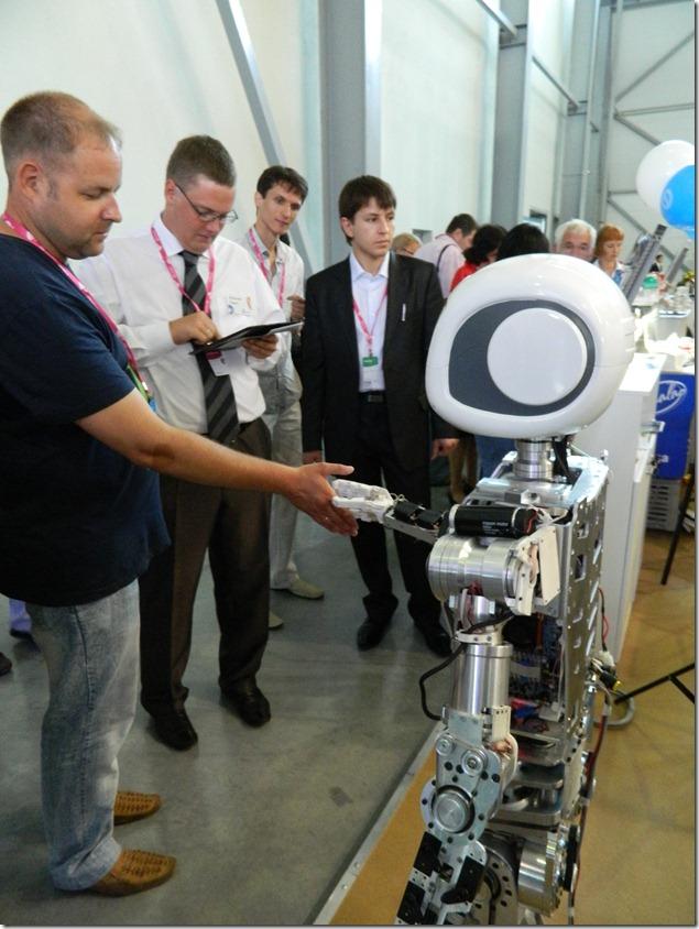 Дмитрий Моисеев здоровается с роботом на Иннпроме