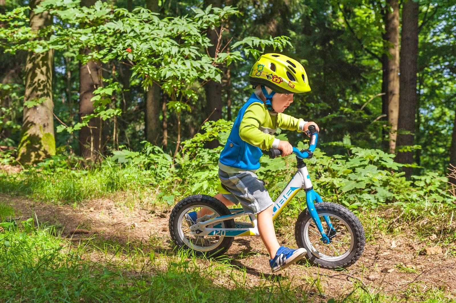 мальчик едет на детском велосипеде